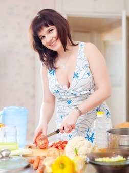 Mooie vrouw die de rode tomaten snijdt
