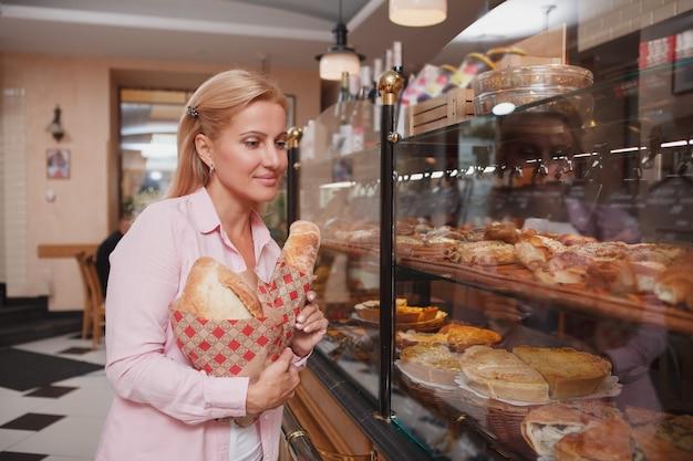 Mooie vrouw die desserts kiest om te kopen bij de showcase van de bakkerij