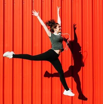 Mooie vrouw die dichtbij rode muur springt