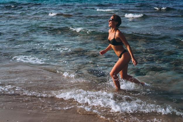 Mooie vrouw die door de oceaan loopt