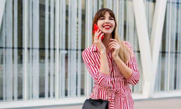 Mooie vrouw die door mobyle telefoon in rode kleding spreekt