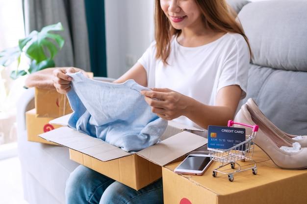 Mooie vrouw die dozen postpakket met smartphone, pakketdozen, creditcard op bank openen. online winkelen, e-commerce, nieuw normaal concept. detailopname