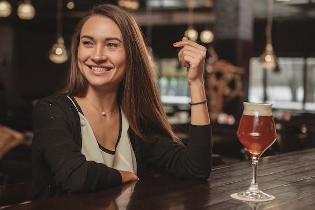 Mooie vrouw die drinkend bier genieten bij lokale bar