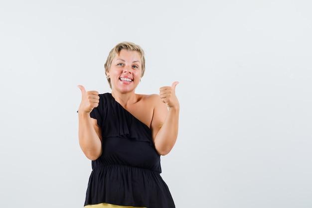 Mooie vrouw die duim in zwarte blouse toont en tevreden kijkt.