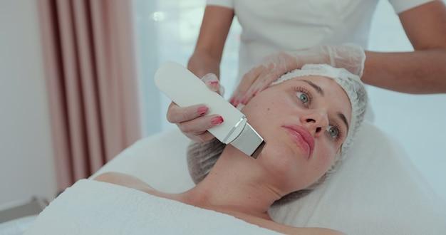 Mooie vrouw die echografie cavitatie gezichtspeeling krijgt. cosmetologie en gezichtsverzorging.