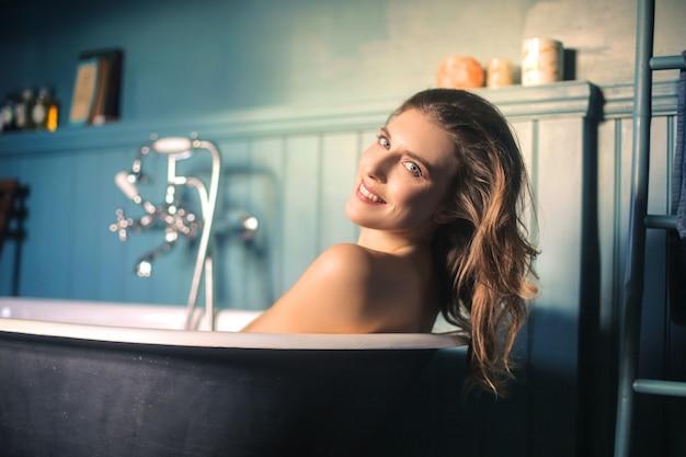 Mooie vrouw die een bad in een elegante antieke badkamers heeft