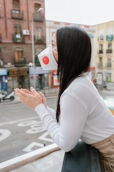 Mooie vrouw die een beschermingsmasker draagt en in het balkon klapt