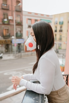 Mooie vrouw die een beschermingsmasker in het balkon thuis draagt