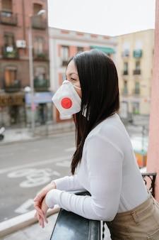 Mooie vrouw die een beschermingsmasker op het balkon draagt