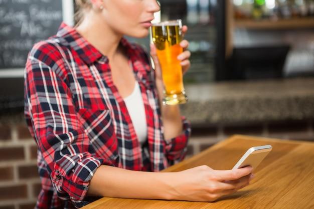 Mooie vrouw die een bier heeft en smartphone bekijkt