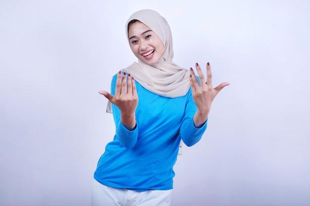 Mooie vrouw die een blauw t-shirt en hijab draagt en iemand uitnodigt om hier te komen