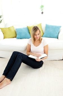 Mooie vrouw die een boek in de woonkamer leest