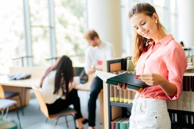 Mooie vrouw die een boek in een bibliotheek leest en denkt