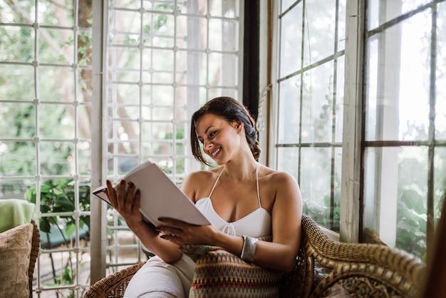 Mooie vrouw die een boek in een serre of een serre leest die zich in de tuin uitbreidt.