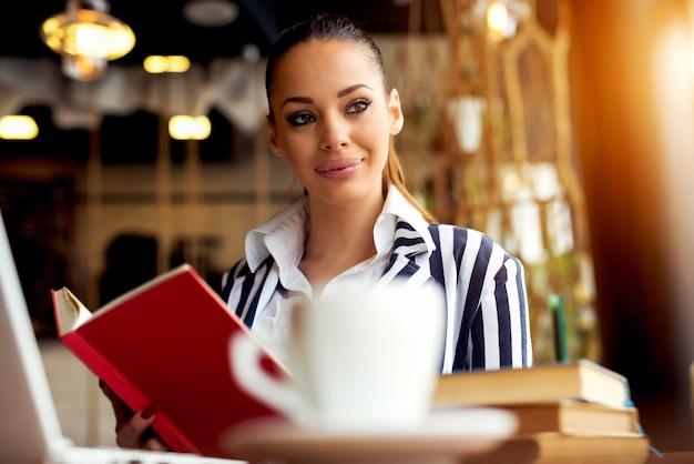 Mooie vrouw die een boek leest bij moderne bibliotheek.