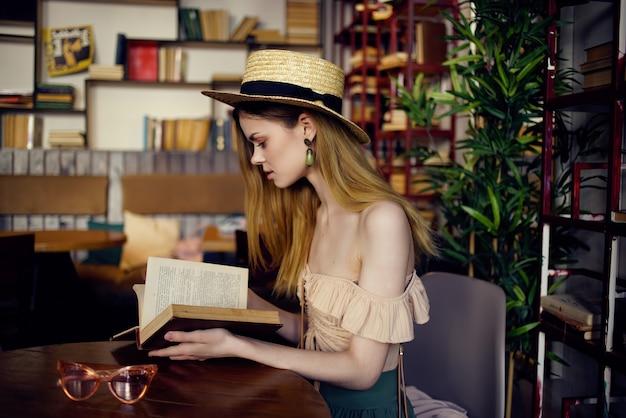 Mooie vrouw die een boek leest in een café-levensstijl
