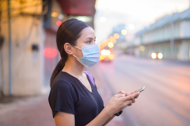 Mooie vrouw die een chirurgisch masker buiten draagt, covid-19, gezondheids- en vervuilingsconcept.