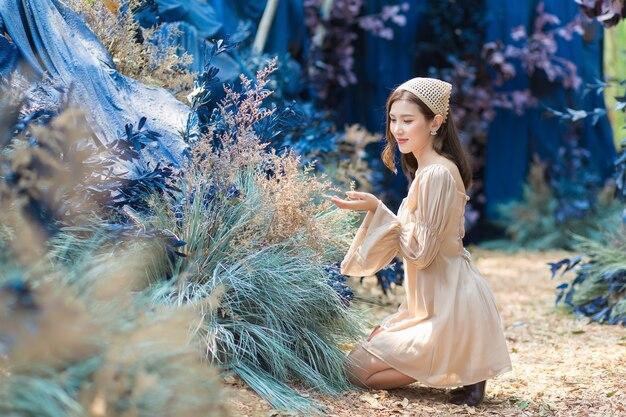 Mooie vrouw die een crèmekleurige jurk draagt, zit op de grond en ziet de bloementuin als natuurlijk
