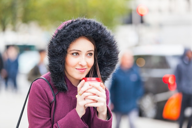 Mooie vrouw die een cuf van thee in londen houdt