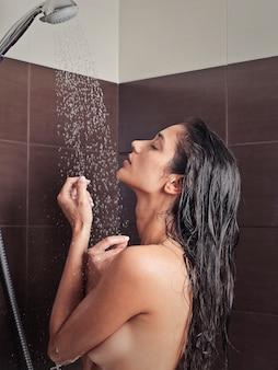 Mooie vrouw die een douche neemt