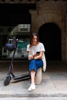 Mooie vrouw die een eco-scooter gebruikt
