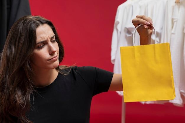 Mooie vrouw die een gele het winkelen zak bekijkt