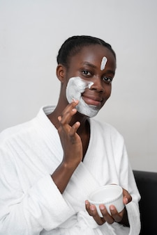 Mooie vrouw die een gezichtsbehandeling thuis doet