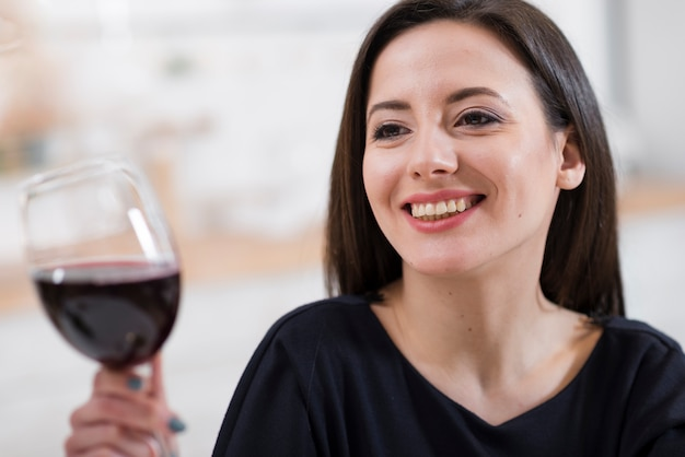 Mooie vrouw die een glas rode wijnclose-up houdt