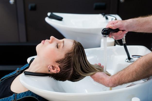 Mooie vrouw die een haarwas in schoonheidssalon krijgt