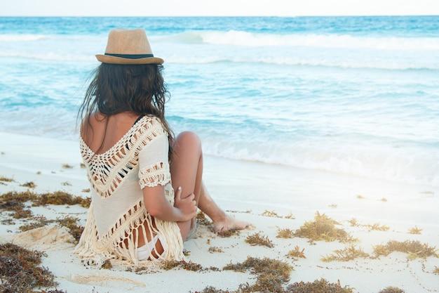 Mooie vrouw die een hoed op het strand draagt