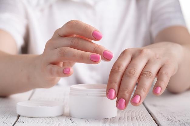 Mooie vrouw die een huidverzorgingsproduct, vochtinbrengende crème of lotion gebruikt die haar droge teint verzorgt. hydraterende crème in vrouwelijke handen
