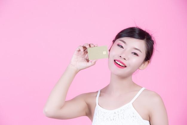 Mooie vrouw die een kaart op een roze achtergrond houdt.
