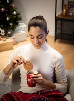 Mooie vrouw die een kop van koffie bekijkt