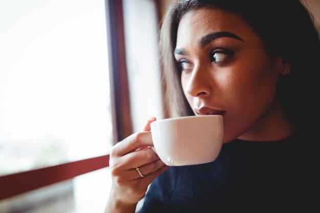 Mooie vrouw die een kop van koffie in koffiebar heeft