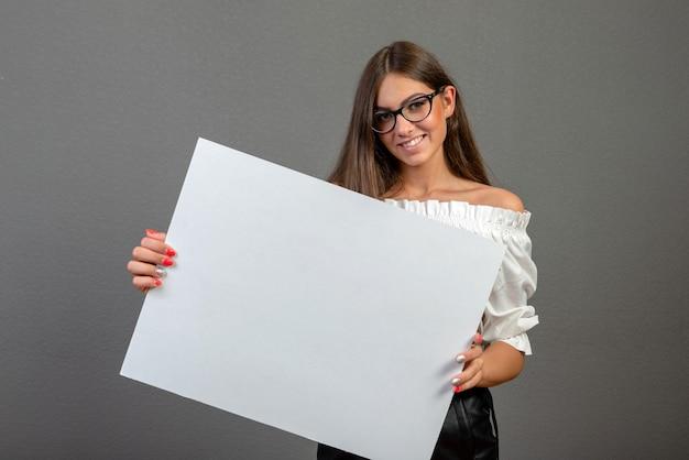 Mooie vrouw die een leeg aanplakbord houdt dat op grijze achtergrond wordt geïsoleerd
