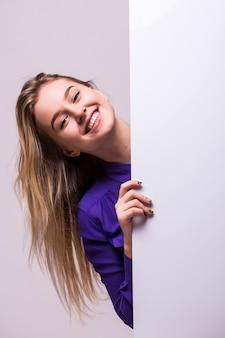 Mooie vrouw die een leeg aanplakbord houdt dat op witte muur wordt geïsoleerd