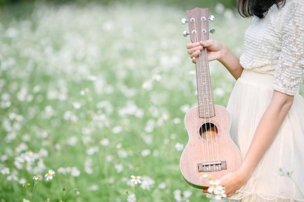Mooie vrouw die een leuke witte kleding draagt en een ukelele houdt