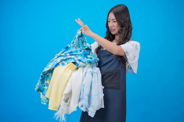 Mooie vrouw die een mand kleren op blauw houdt