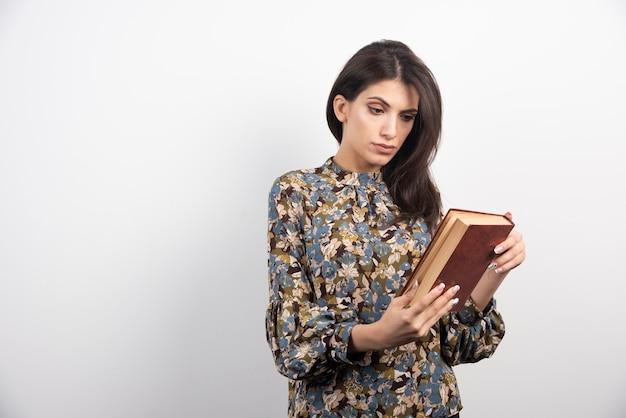 Mooie vrouw die een naam uit het boek leest.
