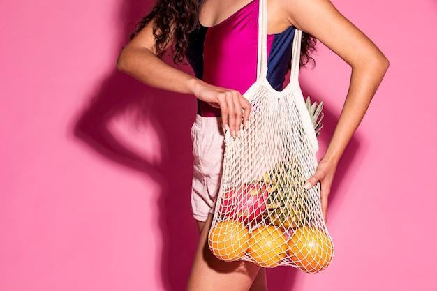 Mooie vrouw die een netzak gebruikt bij het kopen van fruit