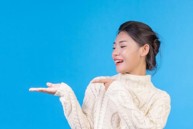 Mooie vrouw die een nieuw wit tapijt met lange mouwen draagt, dat een gebaar op een blauw toont. handel.