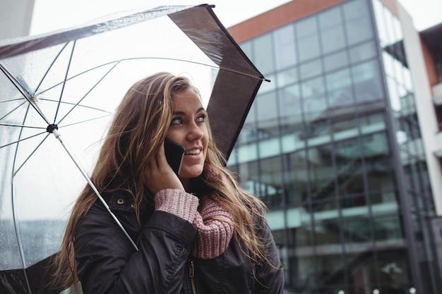 Mooie vrouw die een paraplu houdt en op mobiele telefoon spreekt