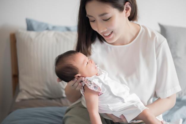 Mooie vrouw die een pasgeboren baby in haar wapens houdt