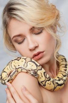 Mooie vrouw die een python houdt, die zich rond haar lichaam wikkelt