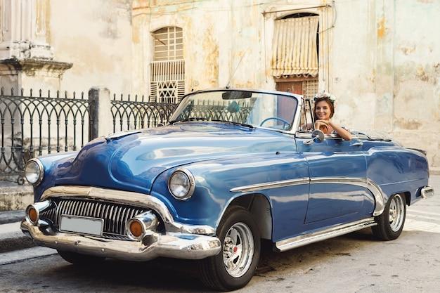 Mooie vrouw die een retro converteerbare auto drijft bij de stad van havana
