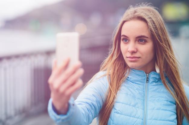 Mooie vrouw die een selfie neemt. mooi meisje dat op straat loopt en enkele oriëntatiepunten fotografeert. blondje nam foto's van zichzelf,