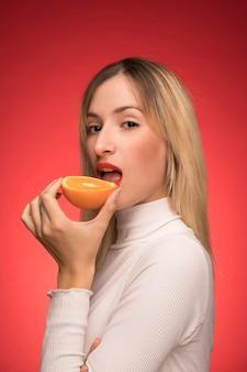 Mooie vrouw die een sinaasappel bijt