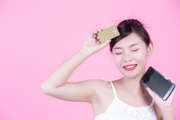 Mooie vrouw die een smartphone en een kaart op een roze achtergrond houdt