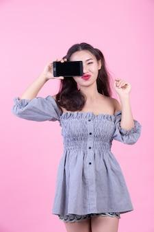 Mooie vrouw die een smartphone op een roze achtergrond houdt.