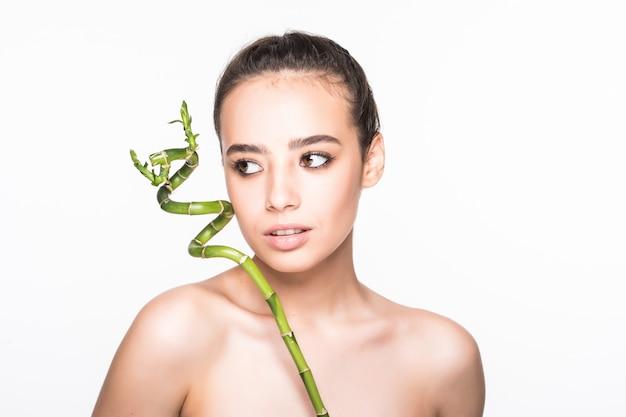 Mooie vrouw die een stok van bamboe op een witte muur houdt
